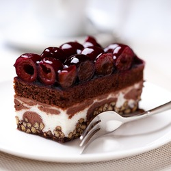 Chocolate Cake with Sour Cherries. Piece of Cake on a Plate. Sweet food. Sweet dessert. Close up.