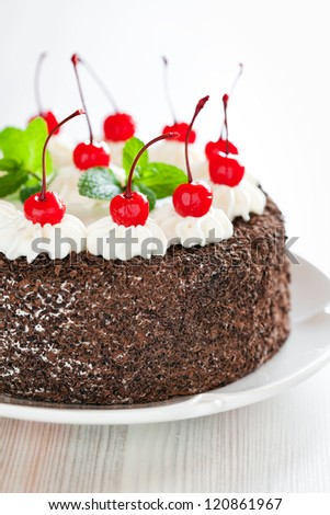 Chocolate cake with whipped cream and glazed cherries, selective focus