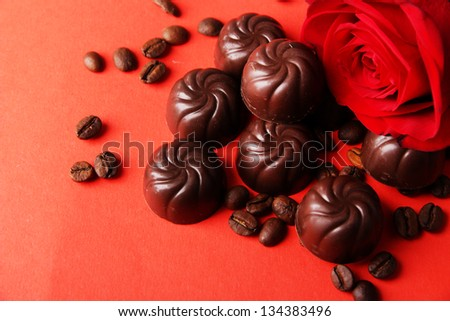 Chocolate candies and coffee beans, on red background