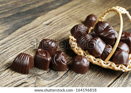 Chocolate candy in wicker basket and near on wooden background