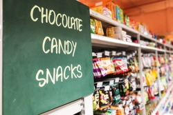 Chocolate, Candy, Snacks signage at the aisle of supermarket with defocused merchandise on shelf