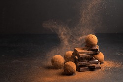 Chocolate candy truffle with chocolate pieces and flying cocoa powder on a dark background