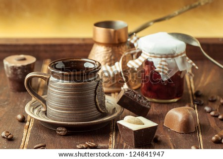 Chocolate candy with cup of coffee and coffee beans on wooden table