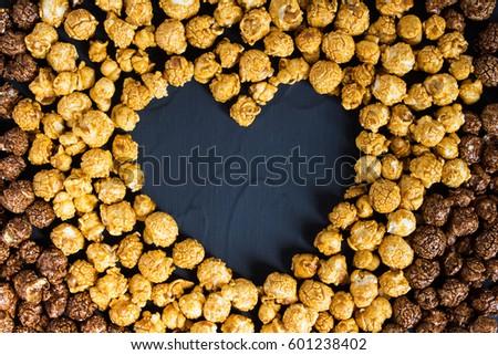 Chocolate caramel popcorn with heart shape. Love popcorn concept. Horizontal photo. Sweet food