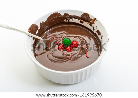 Chocolate & Cherries.Close up of melted chocolate in a white pot. Delicious and popular sweet staple. Texture and highlights in one of the most popular sweet food.
