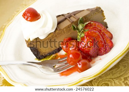 Chocolate Cherry Cheesecake slice on a plate with cherry topping and strawberry garnish, great for Valentine's Day