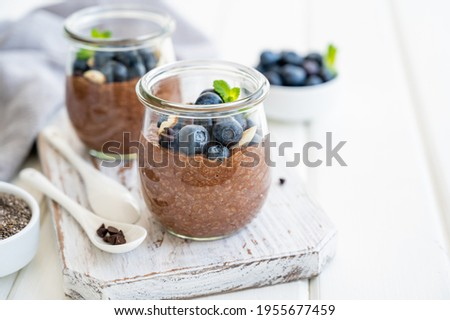 Chocolate chia pudding with blueberry, almonds and mint on top in a glass jar on a white wooden background. Healthy food. Copy space Stock photo ©