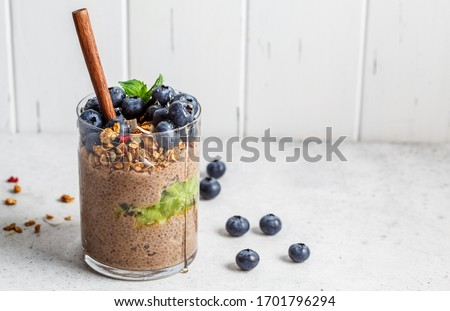 Chocolate chia pudding with fruits, granola and berries in a glass. Foto stock ©