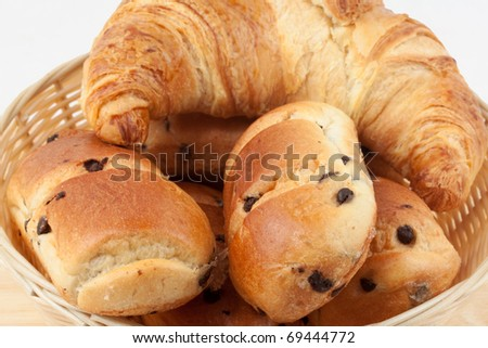 Chocolate chip brioche rolls with croissant in basket