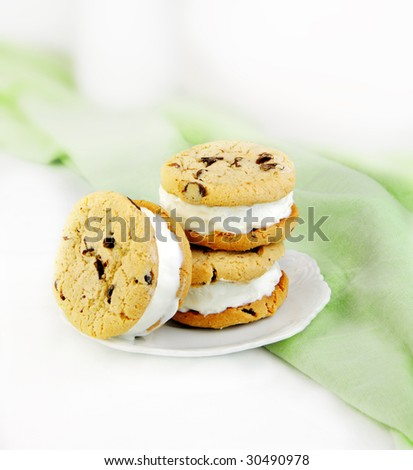 Chocolate chip cookie and ice cream sandwiches on green and white background. - stock photo