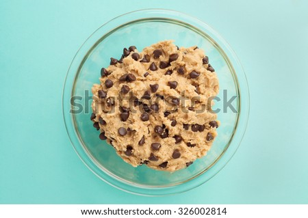 Chocolate chip cookie dough in a glass bowl on a blue table cloth. Stock photo ©