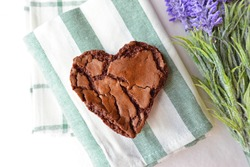 Chocolate chip cookie in the shape of heart, with purple flowers. Concept about love and relationship.