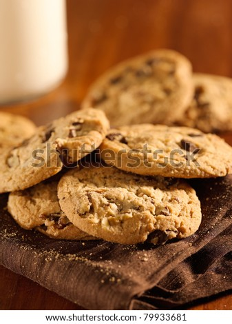 chocolate chip cookies and glass of milk in background