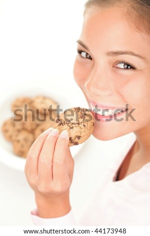 Chocolate chip cookies eating. Cute mixed race chinese / caucasian model on white background.
