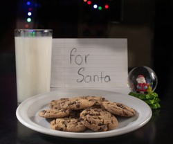 Chocolate chip cookies for santaclaus with a glass of milk behind