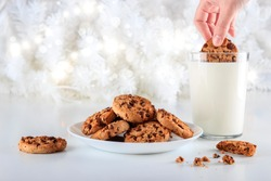 Chocolate chip cookies handmade on a plate. A woman's hand dips a cookie in a glass of fresh milk on Christmas day. The lights are on decorating the white Christmas tree. Christmas holidays concept.