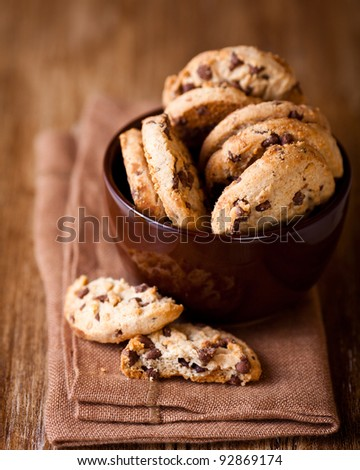 Chocolate chip cookies in a coffee cup. Symbolic image. Concept for a tasty snack. Sweet dessert. Rustic wooden background. Selective focus. Close up.  #92869174