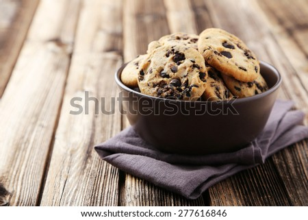 Chocolate chip cookies in bowl on brown wooden background