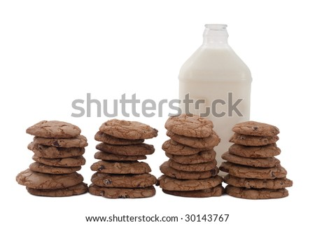 Chocolate chip cookies in four stacks, with a bottle of milk behind