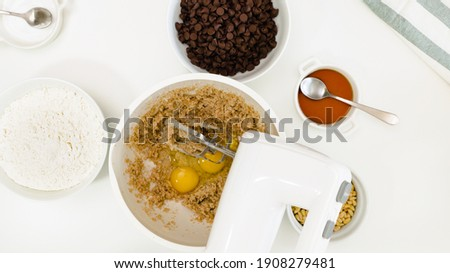 Chocolate Chip Cookies recipe. Mix of butter, sugar and eggs in a bowl, close up on white background, view from above Foto stock ©