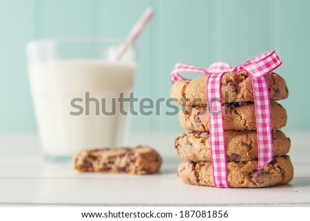 Chocolate chip cookies with a pink ribbon and a glass of milk with a straw on a white wooden table with a robin egg blue background. Vintage look.