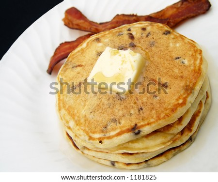 chocolate chip pancakes with butter, syrup and a side of bacon