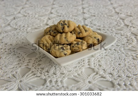 Chocolate chips cookies stacked up on a white plate.  Side view of the cookies displayed on a table covered by a white lace table cloth.