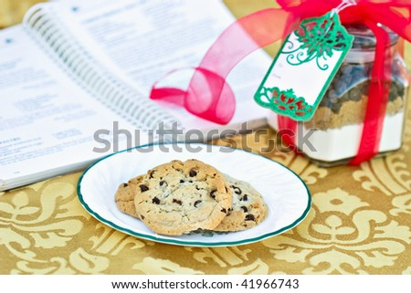 Chocolate Chips Cookies with a gift of cookie mix in a jar with blank card. Shallow DOF with cook book in the background.