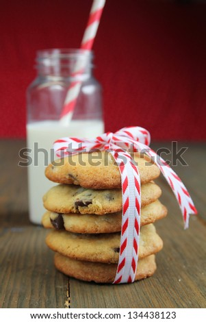 Chocolate chips cookies with white and red ribbon and a bottle of milk in the background
