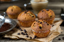 Chocolate chips muffins with coffee on wooden background