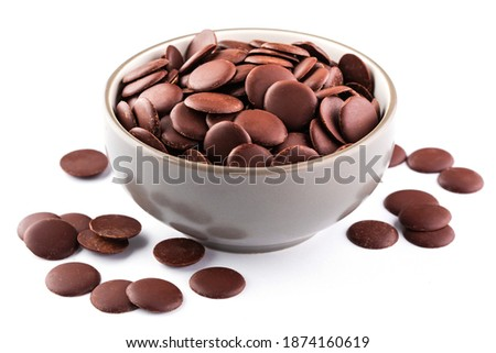 Chocolate chips or granules for making melted chocolate in a bowl on white background. Confectionery chocolate. Chocolate round sweets.