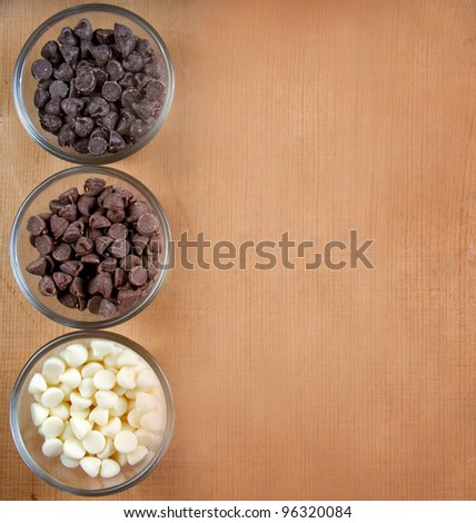 Chocolate chips three kinds in glass containers, wood background.