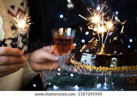 chocolate christmas cake with bengal lights in hands #1187245969