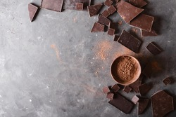Chocolate  chunks and cocoa powder on a gray background.