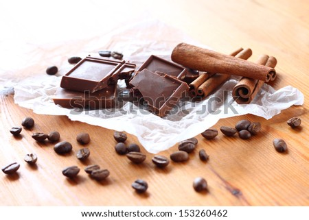 chocolate, cinamon and coffee beans on wooden table. selective focus. natural light.
