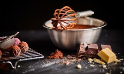 Chocolate coated whisk resting on mixing bowl filled with melted chocolate or sauce with a wire rack of bonbons and ingredients