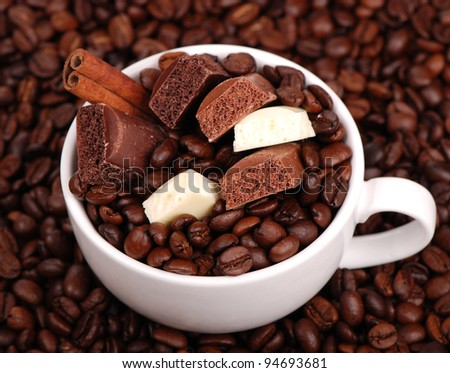 chocolate, coffee beans and cinnamon in a coffee cup/White cup with coffee beans
