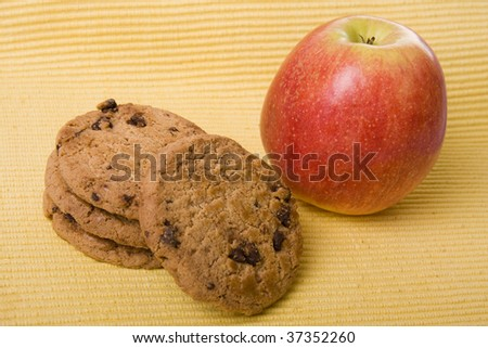 Chocolate cookies and a red apple on a yellow background - stock photo