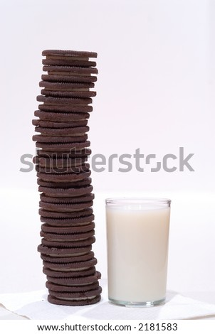 Chocolate Cookies and Milk - Chocolate frosting-filled cookies stacked high on a napkin alongside a glass of cold milk.