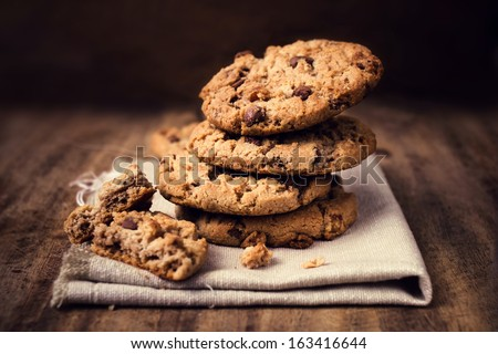 Chocolate cookies on white linen napkin on wooden table. Chocolate chip cookies shot on coffee colored cloth, closeup. #163416644