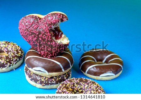 chocolate-covered donuts in the shape of a heart with a bitten off piece and sprinkled with decorative sprinkles on a blue background.
