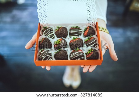 chocolate covered strawberries.  in the woman hands