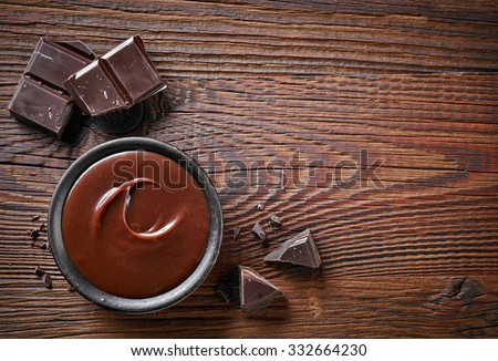 Chocolate cream and chocolate pieces on wooden table, top view