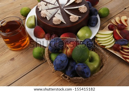 chocolate cream brownie cake layers slice topped with white chocolate and cream flowers decorated with fruits apple plum and grape on plate on wooden table with big whole cake - stock photo