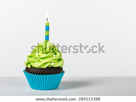 Chocolate Cupcake decorated with green icing, sprinkles and a lit birthday candle on a white background.