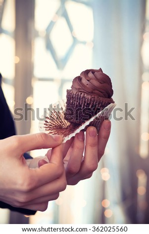 Stock Photo Chocolate cupcake in the hands of baker