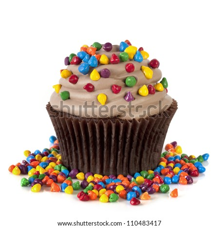 Chocolate cupcake topped with colorful sprinkles.  Isolated on white.