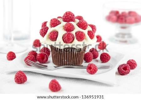 Chocolate cupcake topped with whipped cream and raspberries on a plate
