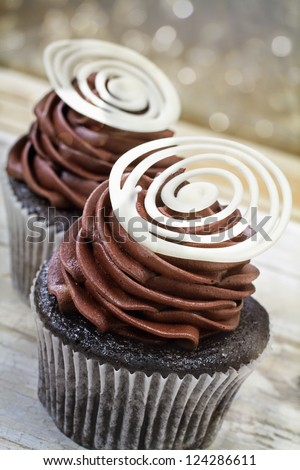 Chocolate cupcake with chocolate mousse cream icing on grunge wooden background with bokeh lights - stock photo
