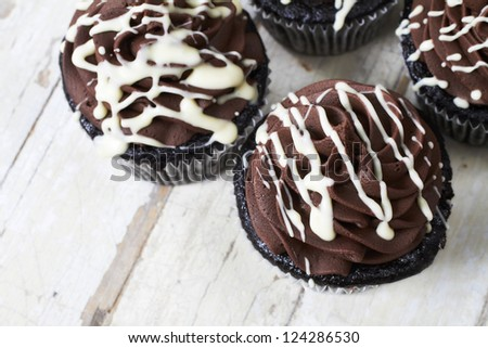 Chocolate cupcake with chocolate mousse cream icing on grunge wooden background with copy space